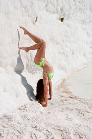 Mind and body in harmony. Sexy woman with fit suntan body. Natural travertine. Beach yoga. Cotton castle in Turkey. Sport. Summer vacation in Pamukkale. Dead sea salty. Sexy girl gymnast in handstand.