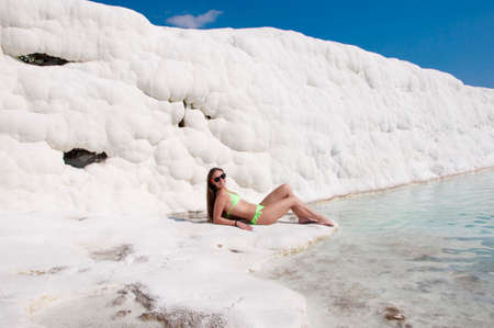 Stress removing. Natural travertine pool terrace in Pamukkale. Sexy woman with fit suntan body. Cotton castle in southwestern Turkey. Summer vacation in Pamukkale. Dead sea salty shore. Sexy girl. Stock Photo
