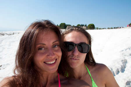 Collecting memories. Selfie. Dead sea salty shore. Sexy girl. Friendship. Summer vacation. Natural travertine in Pamukkale. Beach. Cotton castle in Turkey. Happy frineds girls with suntan.