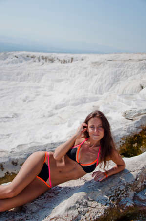 Summer vacation in Pamukkale. Sexy woman with fit suntan body. Cotton castle in Turkey. Dead sea salty shore. Sexy girl. Natural travertine pool terrace in Pamukkale. Enjoying youth and freedom.