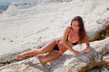 Dead sea salty shore. Sexy girl. Cotton castle in southwestern Turkey. Summer vacation in Pamukkale. Natural travertine pool terrace in Pamukkale. Sexy woman with fit suntan body. Girl in sauna. Stock Photo