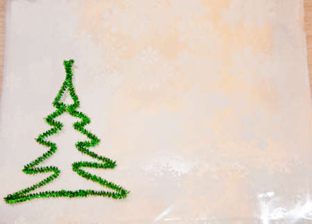 merry christmas. xmas congratulation time. let it snow. decorate tree. new year greeting card. copy space. green christmas tree from tinsel on snowflakes white background. snowy winter weather.