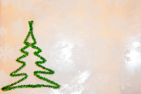 new year greeting card. copy space. green christmas tree from tinsel on snowflakes white background. snowy winter weather. merry christmas. xmas congratulation time. let it snow. decorate tree.