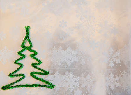 copy space. green christmas tree from tinsel on snowflakes white background. snowy winter weather. merry christmas. xmas congratulation time. let it snow. decorate tree. new year greeting card.