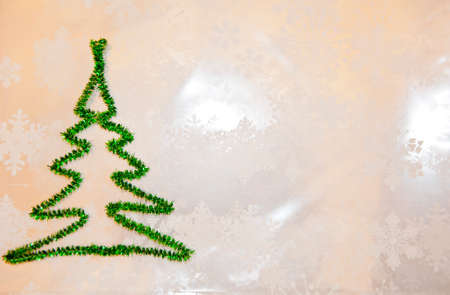 snowy winter weather. merry christmas. xmas congratulation time. let it snow. decorate tree. new year greeting card. copy space. green christmas tree from tinsel on snowflakes white background.