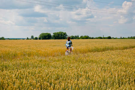 caucasian girl riding bicycle on wheat field, countryside ukraine. vintage photo. Girl on a bike in the countryside. Portrait of a sexy brunette in the hayloft. young woman on bicycle in hay ranch.
