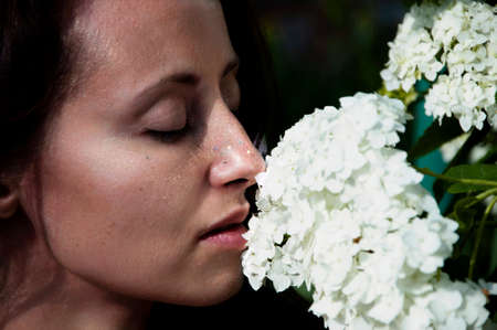 woman smelling beautiful hydrangea bouquet. Countryside lifestyle gardening. Fashionable girl with flowers. perfect skin. organic cosmetic care. natural makeup. spa and beauty salon. spring allergic.