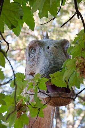 Diplodocus eating green leaves. Dinosaur in the park. Brachiosaurus dinosaurs toy in tree leaves.