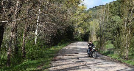 rebeldia: De mejor joven conducía su motocicleta tipo crucero en el camino forestal. Foto de archivo