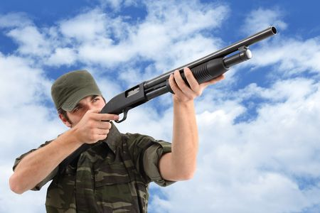 guerilla: A man (soldier, hunter, guerilla, etc.) wearing a camouflage clothing is aiming with his pump action shotgun and cloudy sky background. Stock Photo