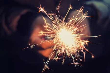 bright festive Christmas sparkler in hand toning