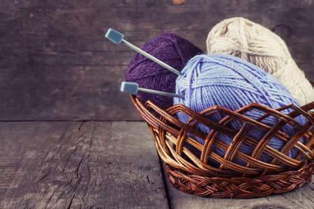 basket embroidery: Skeins colored yarn and knitting needles in a basket on a wooden background
