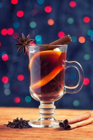 creates: toned photo of a glass of mulled wine with spice on the bokeh  background creates Christmas festive atmosphere