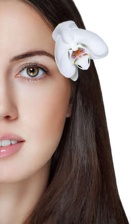 Closeup on beautiful face with white orchid flower, perfect clean skin, young female portrait, beauty and spa concept Stock Photo