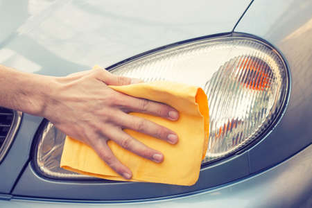 waterless: waterless car wash. Mens hand with yellow cloth cleaning headlight of car photo with toning. Polishing car to shine