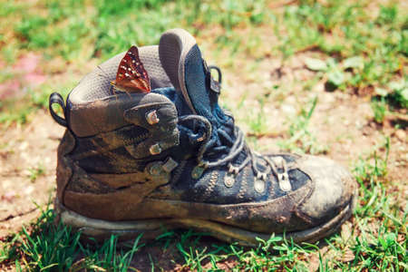 walking boots: dirty old shoe on ground. Retro faded photo of dirty walking boots in green grass. Muddy hiking boot drying at the green meadow to illustrate the concept of adventure in the outdoors
