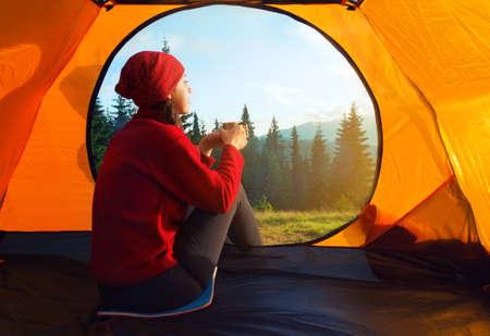 山の風景のテントの中からの眺め。キャンプのコンセプトです。テントの中の夕日。山の風景を見てカップをテントの中で座っている若い女性