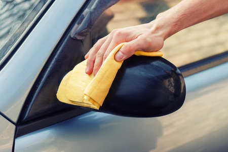 waterless: waterless car wash. Mens hand with yellow cloth cleaning car photo with toning. Washing the car by hand with rag. Cleaning the car. Car care concept. Hand of man washing the car using the sponge