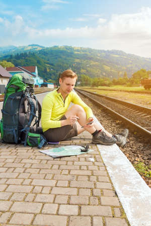 man tourist sitting with smartphone, map and travel bag at the train station. Traveler holding smartphone, waiting for a train at train station and planing for next trip. Stock Photo