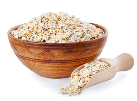 Oat flakes in clay bowl and wooden scoop isolated on a white background. Healthy food. Healthy groats. Ceramic bowl with cereals. Oatmeal