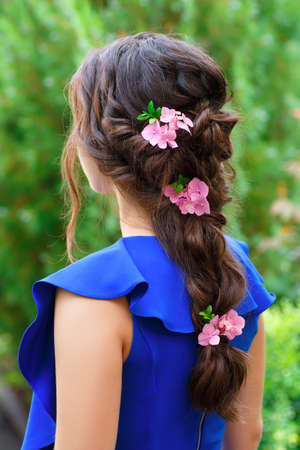 elegant hairstyle with fresh flowers in a plait . Woman with fashion wedding hair on nature background. Hairstyle. Wedding, flower decorations in the hair of the bridesmaid Archivio Fotografico