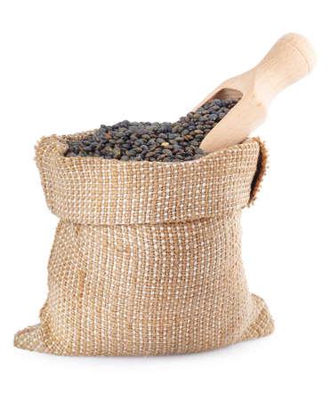 super food: black lentils with wooden scoop in burlap bag isolated on white background. Black beluga lentils. Super food