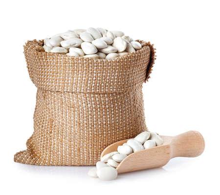 Fagioli di burro o fagioli di lima nella borsa di tela da imballaggio con la paletta di legno isolata su fondo bianco. Fagioli bianchi secchi nel sacco di iuta. fagioli