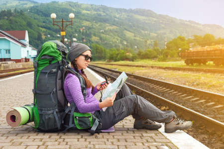 Happy girl tourist with backpack sits on a platform waiting for a train. Travel concept. Traveler holding map, waiting for a train and planing for next trip. Traveler reading map Stock Photo