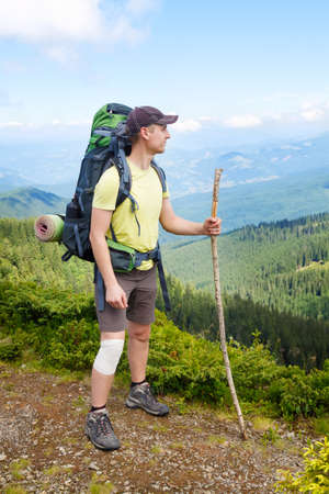 Young hiker with bandage on knee and cane in hand in mountains. Male wearing shorts on top of mountain with wrapped injured knee with white sports bandage. Hiking Stock Photo