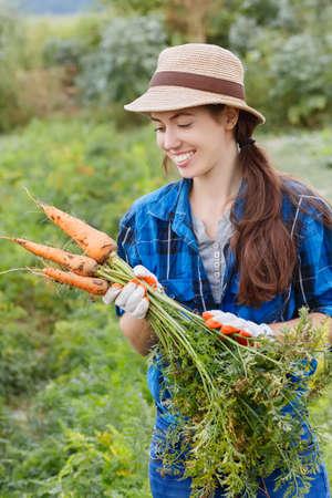 Gardening. Woman with organic carrots in a vegetable garden. Happy girl harvesting carrots in field. Gardener with carrots in garden. Harvest. Young farmer harvesting carrots. Foto de archivo