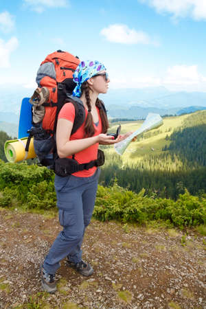 determines: Woman tourist in mountain determines the direction with a compass and map. Hiker watching the map. Girl tourist with map and compass. Lifestyle concept active leisure tourism. Hiking