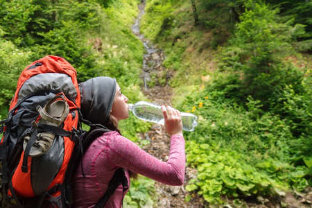 Hiker girl drinking water. Woman tourist with backpack drinking water in nature. Young tourist woman drinking water outdoor, forest and source of spring water on the background. Woman with bottle of water Stock Photo
