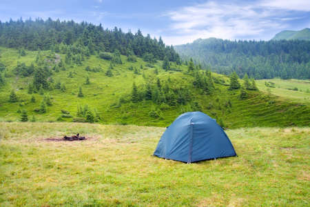 View of tent on meadow in mountains. Camping background. Camping and tent. Tourist tent on meadow green pine forest, mountains and sky on the background. Adventure travel active lifestyle freedom outdoors.