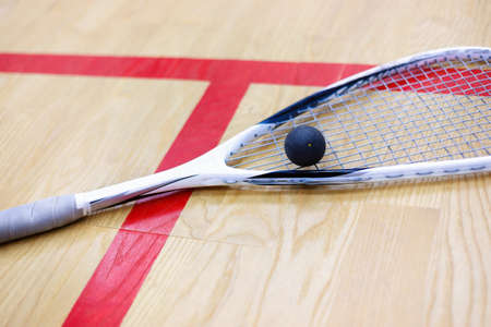 racquetball: squash racket and ball on the wooden background. Racquetball equipment. Squash ball and squash racket on the court next to a red line. Photo with selective focus