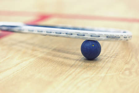 racquetball: Close up of a squash racket and ball on the wooden background. Racquetball equipment. Squash ball between squash racket and floor on the court. Photo with toning and selective focus Foto de archivo