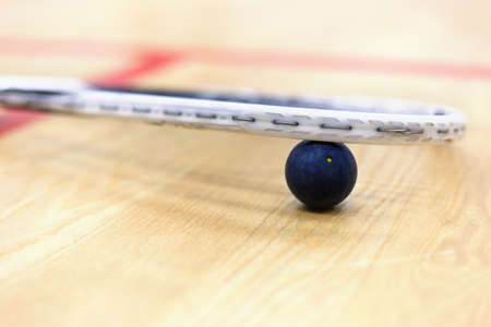 racquetball: Close up of a squash racket and ball on the wooden background. Racquetball equipment. Squash ball between squash racket and floor on the court. Photo with selective focus