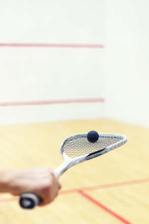 racquetball: squash racket and ball in mens hand. Racquetball equipment. Squash ball on squash racket with court on the background. Photo with toning and selective focus
