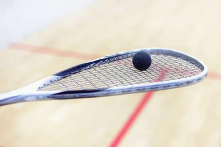 racquetball: raqueta de squash y pelota. Equipo de Racquetball. Bola de calabaza en la raqueta de squash con corte en el fondo. Foto con tono y enfoque selectivo