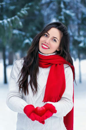 Girl in winter forest with heart
