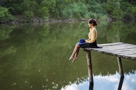 young woman sitting by the lake