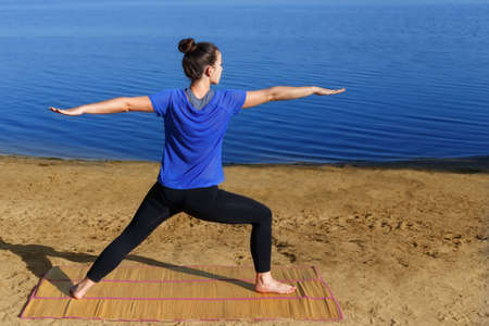Woman practicing yoga outdoors Stock Photo