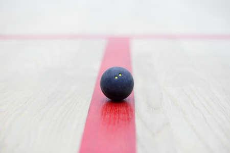 racquetball: Bola de calabaza en el fondo de madera. Equipo de Racquetball. Squash bola en la cancha en la línea roja. Foto con enfoque selectivo