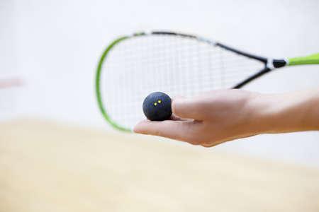 racquetball: raqueta de squash y pelota en las manos del hombre. Equipo de Racquetball. Foto con enfoque selectivo. El jugador se prepara para servir una pelota. Primer plano de la bola de servir de mano masculina Foto de archivo