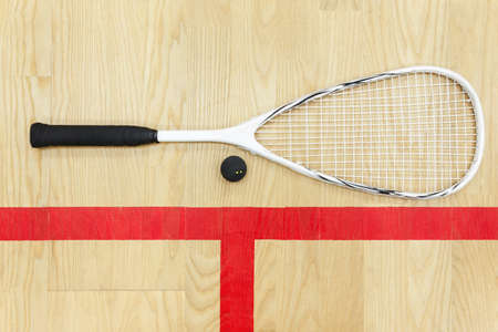 white squash racket and ball on the wooden floor top view. Racquetball equipment on the court near red line