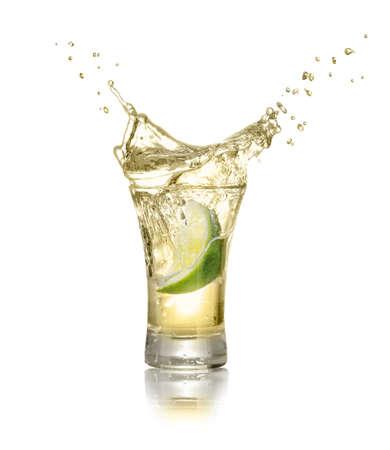 ゴールド テキーラはライムのスライスとスプラッシュは、白い背景で隔離で撮影。ライムは、アルコール飲料で落ちています。テキーラはライムの