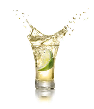 gold tequila shot with lime slice and splash isolated on white background. Lime is falling in the alcohol drink. Splash of tequila from the falling piece of lime