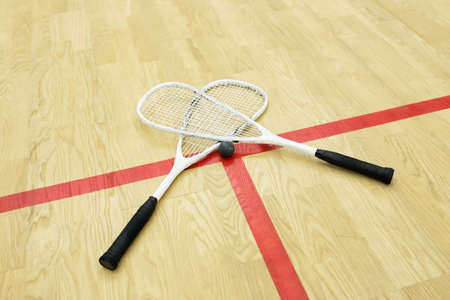 racquetball: squash rackets and ball on the court near red line. Racquetball equipment. Photo with selective focus