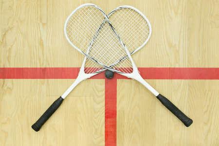 racquetball: dos raquetas de squash cruzadas y bola en la vista superior del piso de madera. Equipo de racquetball en la cancha cerca de la línea roja. Foto con enfoque selectivo Foto de archivo