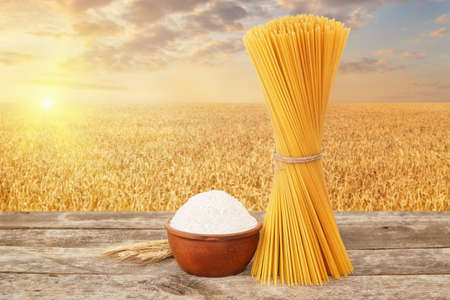 bundle of uncooked spaghetti and wholemeal flour in bowl on table with ripe cereal field on the background. Golden wheat field on sunset. Photo with place for text