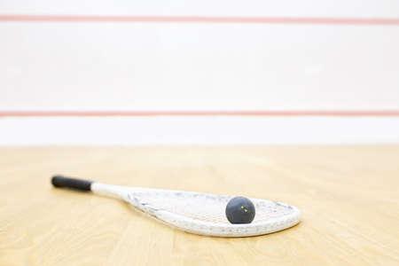 racquetball: Raqueta y pelota para juego de squash. Equipo de Racquetball en la cancha y la pared con líneas rojas en el fondo. Foto con enfoque selectivo